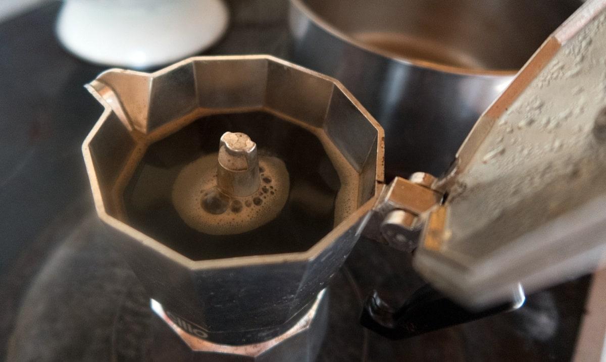 caffè fuoriesce da caffettiera moka sul fuoco