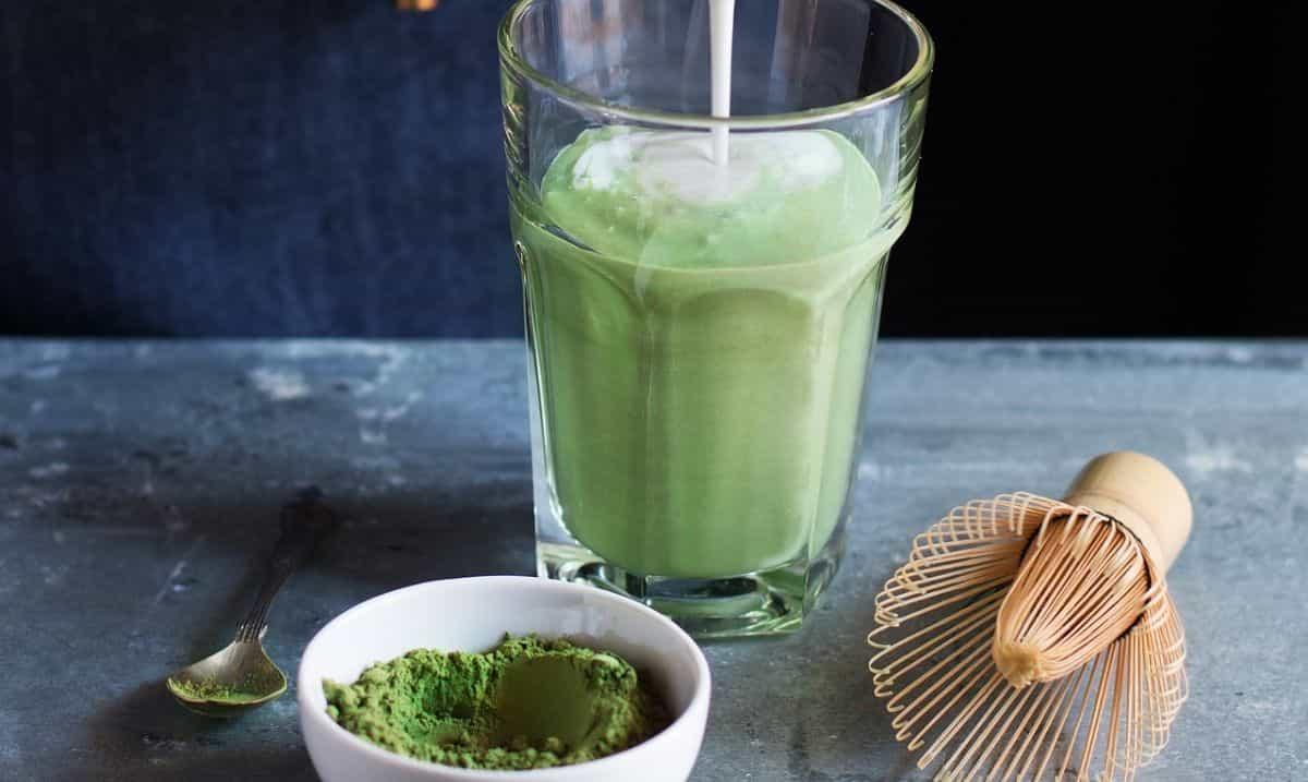 Matcha latte in bicchiere e tè verde matcha in polvere