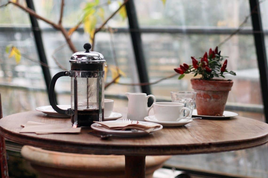 caffettiera french press poggiata su tavolino insieme a tazzine di caffè