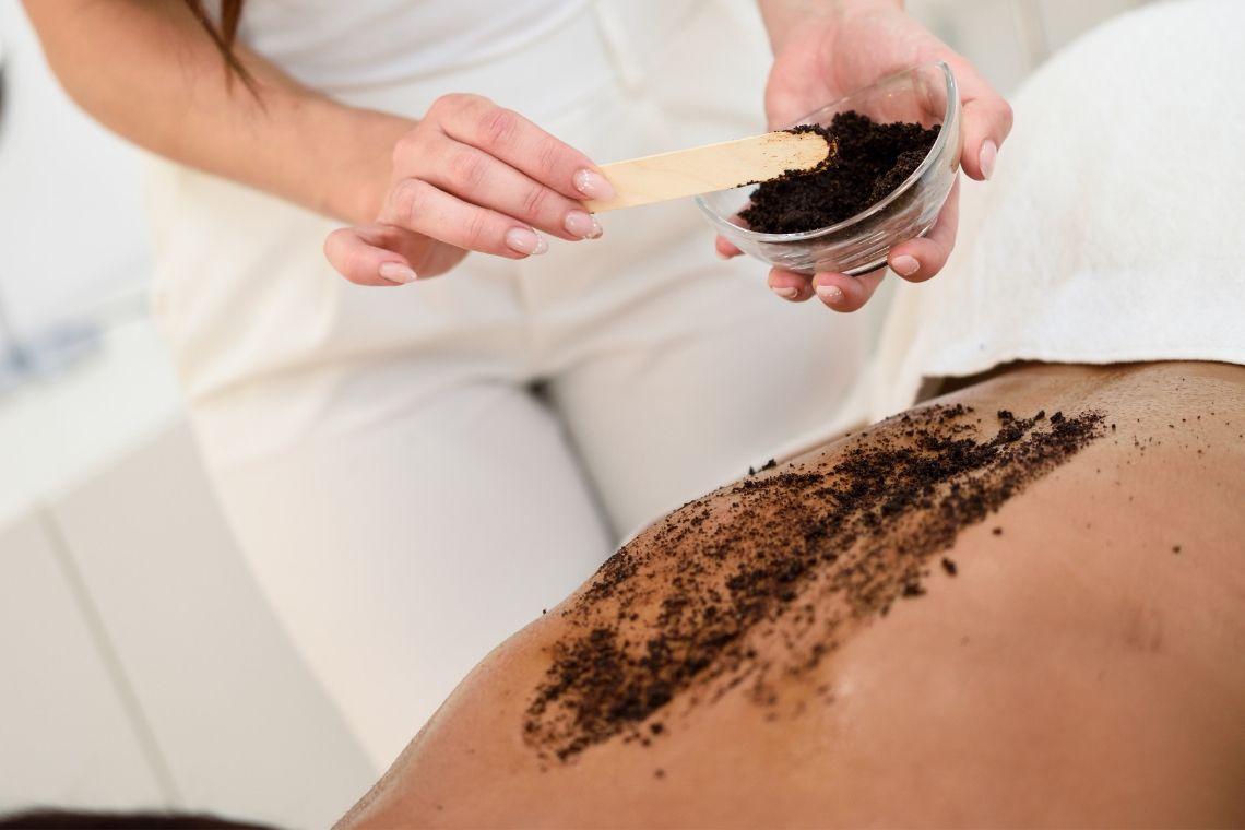 applicazione dello scrub al caffè anticellulite su donna distesa