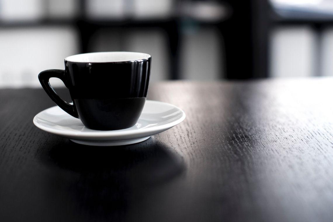 tazzina nera di caffè su tavolo in legno