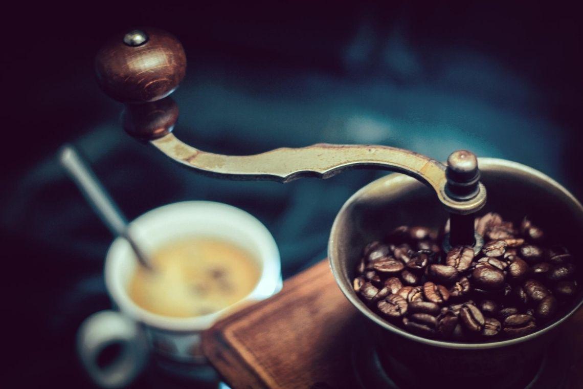 macinino con chicchi di caffè in grani nel cestello