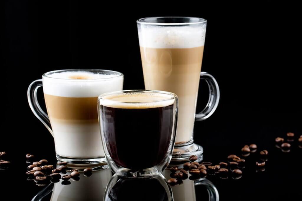 tazzine e bicchieri con differenti tipi di caffè